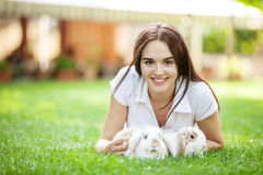 Girl with two pet rabbit in a park Royalty Free Stock Photos