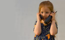 Girl with two phones. Very young girl holding two phones Royalty Free Stock Image