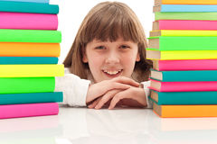 Girl between two piles of books Stock Photo