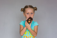 The girl with two plaits biting a chocolate cake Stock Photo