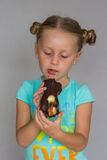 The girl with two plaits biting a chocolate cake Royalty Free Stock Photography