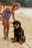 Girl with two plaits and met in a swimsuit on the beach near the sea lovely dog Royalty Free Stock Images