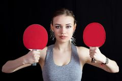 Girl with two rackets for playing table tennis. royalty free stock photography