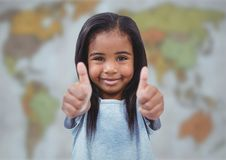 Girl with two thumbs up against blurry map Royalty Free Stock Photos