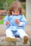 Girl two years, with a cell phone in the park Royalty Free Stock Photography