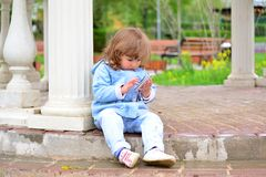 Girl two years, with a cell phone in the park Royalty Free Stock Photos