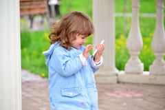 Girl two years, with a cell phone in the park Stock Photography