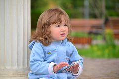 Girl two years, with a cell phone in the park Stock Images