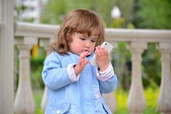 Girl two years, with a cell phone in the park Royalty Free Stock Photo