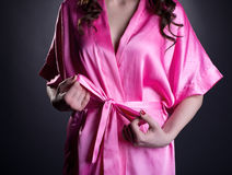 Girl tying belt of her silk robe, close-up Royalty Free Stock Image