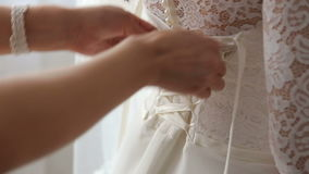 Girl tying the bride`s wedding dress, close-up. Close-up of a girls hand tying the corset on the wedding dress of the bride stock video footage