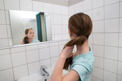 Girl Tying Hair In Bathroom Royalty Free Stock Image
