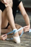 Girl tying her ballet shoes Royalty Free Stock Photos