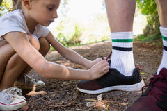 Girl tying her grandfathers shoe laces Royalty Free Stock Image