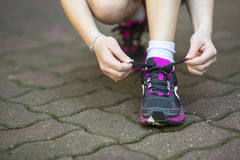 girl is tying the laces sports shoe before running. Stock Photo