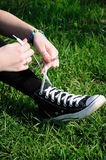 Girl tying shoe. /laces on grass Royalty Free Stock Images