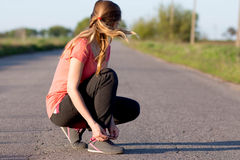 Girl tying shoelaces doing jogging Royalty Free Stock Photo