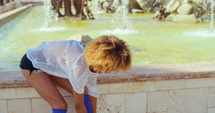 Girl Tying Shoelaces in Her Roller Skates. Slow Motion Video of Girl With Afro Haircut Tying Shoelaces in Her Roller Skates While Sitting on Fountain Wall stock video footage