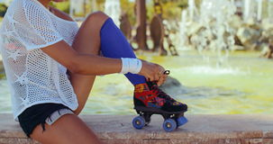 Girl Tying Shoelaces in Her Roller Skates. Slow Motion Video of Girl With Afro Haircut Tying Shoelaces in Her Roller Skates While Sitting on Fountain Wall stock video