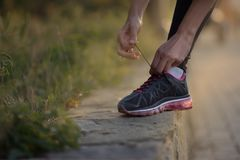 Girl tying shoelaces on running shoes for a run royalty free stock photo
