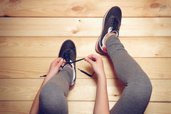 Girl tying shoelaces sitting on the wooden floor Stock Images