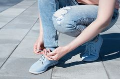 The girl is tying shoelaces on sneakers. royalty free stock photo