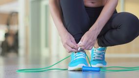 Girl tying shoelaces sneakers and takes a skipping rope.  stock video footage