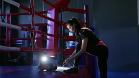 Side view cute brunette girl ties shoelaces sports shoes putting his foot on boxing ring on which boxing gloves lie. Side view cute brunette girl athlete in stock footage