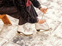 Girl tying skates on the rink Royalty Free Stock Image