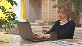 Girl types on laptop at the working hub. Pretty blond girl typing on laptop at the working hub. Attractive caucasian female in glasses keeping her hand on her stock video