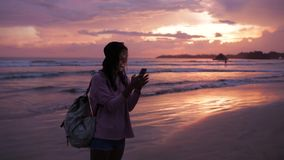 Girl types a message near ocean at sunset stock video