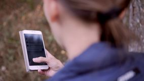 Girl typing on her smart phone in the forest. Girl typing on her smart phone stock footage
