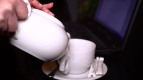 The girl is typing on the laptop keyboard. Hands close-up. The girl pours the tea into a cup. The girl is typing on the laptop keyboard. Close-up. Girl sitting stock video footage