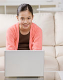 Girl typing on laptop in livingroom Stock Photos