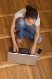 Girl typing on a laptop sitting the parquet floor stock image