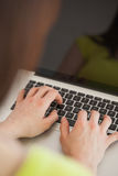 Girl typing on a laptop sitting on a sofa Stock Photo