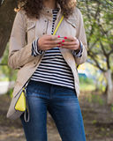 Girl typing a message on her phone in a beige jacket and blue je. A girl stands on the street in the spring on a background of trees, wearing a beige jacket Royalty Free Stock Photos