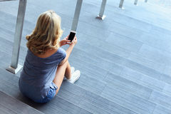 Girl typing message on mobile phone and sitting on stairs Royalty Free Stock Photography