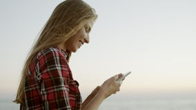 Girl typing a message on sky background. Girl typing a message. girl using phone on sky backround stock video footage