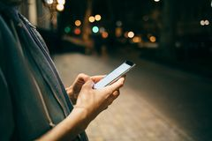 Girl typing message on smart phone on background bokeh lights stock photography