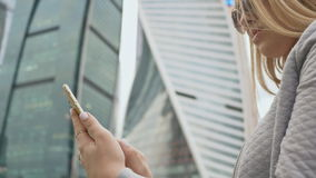 Girl typing on a phone against the background of high-rise buildings in the center of the city. Girl typing on a phone against the background of high-rise stock video footage