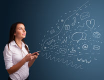 Girl typing on smartphone with various modern technology icons Stock Images