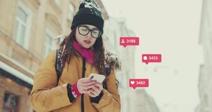 Girl Typing on Smartphone Winter Looks with Snow Background Social Media Icons with Like Comment Follower Counter Quick stock video footage