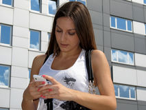 Girl typing sms, texting with building. Young beautiful brunette texting on a mobile phone outdoors in a sun with building background Royalty Free Stock Images