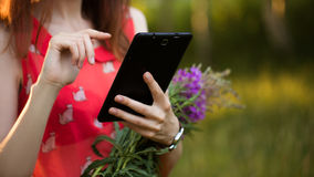Girl is typing on tablet. Pretty girl is keeps tablet pc, typing, looking information, watching film. Red dress, bright make up, flower in hair Royalty Free Stock Photos