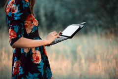 Girl is typing on tablet. Pretty girl is keeps tablet pc, typing, looking information, watching film. Red dress, bright make up, flower in hair Royalty Free Stock Photo