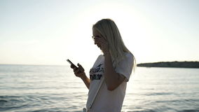Girl typing the text on smartphone at the coast of ocean at sunset background. Happy blonde using the smartphone at the coast of the ocean at the sunset stock video