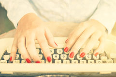 Girl typing on a typewriter, vintage photo effect. Close up Royalty Free Stock Photos