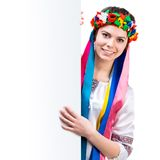Girl in  Ukrainian  costume behind white board Royalty Free Stock Photos