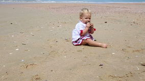 Girl in Ukrainian Costume Embroidery on Beach. Little girl in the national Ukrainian costume embroidery eating stone walking on the beach stock footage